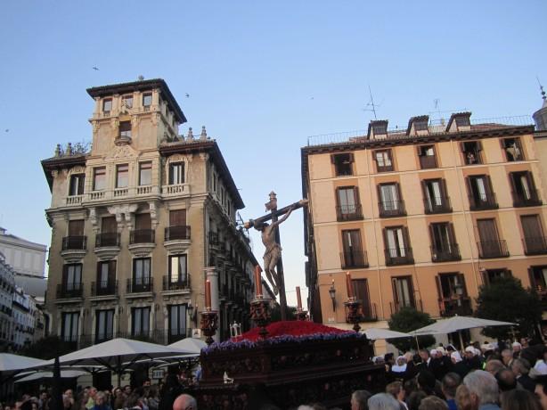 Socha Ukrižovaného Krista v uliciach historického centra Madridu v sprievode množstva ľudí.